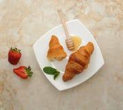 le croissant deux d'un plat blanc a bruiné avec du miel photos stock