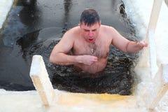 Le croyant orthodoxe prend une immersion dans l'eau glacée Photos stock