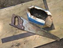 Le cru a vu, les clous et le grand dos du charpentier Photos stock