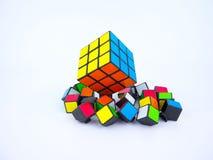 Le cube de Rubik coloré et les morceaux cassés de cube Photos stock