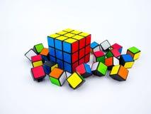 Le cube de Rubik coloré et les morceaux cassés de cube Images libres de droits
