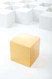 Le cube en or se tient parmi les cubes blancs Photographie stock libre de droits