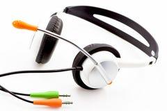 Le cuffie con bianco sgrana le orecchie e un microfono Fotografia Stock
