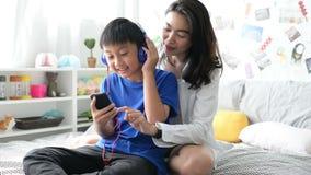 Le cuffie d'uso del figlio e della madre facendo uso dello smartphone per ascoltano insieme musica a casa archivi video