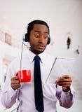 Le cuffie d'uso dell'uomo bello con il microfono, la camicia a strisce bianca ed il legame, tenenti la tazza da caffè, hanno sorp Fotografie Stock Libere da Diritti