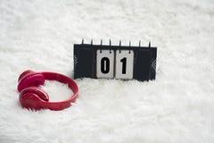 Le cuffie ed i calendari rossi del metallo con il numero 01, sono disposti su un tappeto bianco con il concetto del giorno e del  fotografia stock libera da diritti