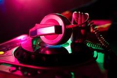 Le cuffie ed il miscelatore professionali DJ per musica in night-club su fondo colorano i laser Immagini Stock Libere da Diritti