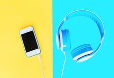 Le cuffie si sono collegate allo smartphone bianco sopra giallo variopinto Fotografie Stock