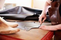 Le cuir de coupe de cordonnier dans un atelier, se ferment  Image stock