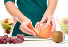 Le cuisinier épluche le pamplemousse pour le dessert de fruit Image libre de droits