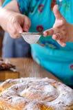 Le cuisinier arrose le sucre sur le gâteau Photographie stock libre de droits