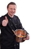 Le cuisinier avec un bac retient son pouce vers le haut photographie stock