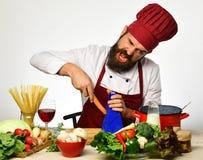 Le cuisinier avec le visage fou s'assied par la table de cuisine avec des légumes Photos stock