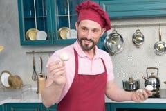Le cuisinier barbu beau tient le champignon Champignons dans des mains du ` s de chef Champignons préparés par homme de sourire p Images libres de droits
