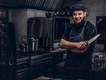 Le cuisinier barbu dans l'uniforme et le chapeau noirs tient le couteau tout en se tenant avec les bras croisés dans la cuisine Image stock