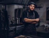 Le cuisinier barbu dans l'uniforme et le chapeau noirs tient le couteau tout en se tenant avec les bras croisés dans la cuisine Photo libre de droits