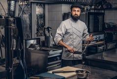 Le cuisinier barbu s'est habillé dans l'uniforme et le chapeau regardant l'appareil-photo dans la cuisine Image stock