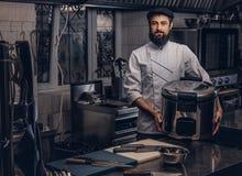 Le cuisinier barbu s'est habillé dans multicooker de prises d'uniforme et de chapeau le grand dans la cuisine Photos libres de droits