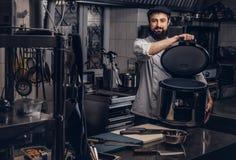 Le cuisinier barbu s'est habillé dans multicooker de prises d'uniforme et de chapeau le grand dans la cuisine Photo stock