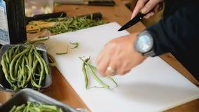 Le cuisinier coupe des cosses de haricot banque de vidéos