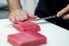 Le cuisinier coupe des filets de thon Photo stock