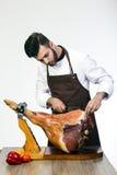 Le cuisinier coupe le jambon Photographie stock libre de droits