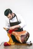 Le cuisinier coupe le jambon Photo stock