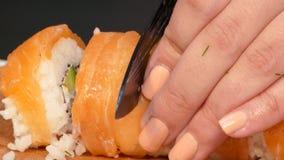 Le cuisinier coupe le petit pain de sushi couvert de la viande saumonée banque de vidéos