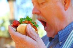 Le cuisinier d'arrière-cour mange le hot-dog avec le piment photos libres de droits