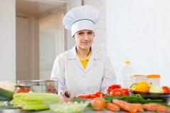 Le cuisinier dans la toque travaille avec la tomate et d'autres légumes images stock