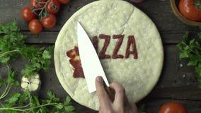 Le cuisinier de chef enduit la sauce tomate sur le mouvement lent de pizza banque de vidéos