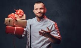 Le cuisinier de chef tient les cadeaux de papier colorés de Noël photo libre de droits