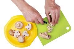 Le cuisinier en chef du restaurant avec un couteau pointu coupe finement Images stock