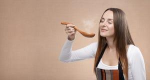 Le cuisinier féminin sent une cuillère de cuisson à la vapeur image stock