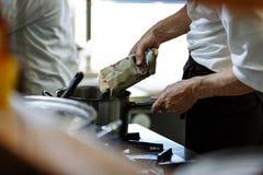 Le cuisinier fait cuire dans une cuisine de restaurant, arrose des épices dans la casserole image libre de droits