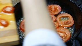 Le cuisinier fait frire des tranches de tomate banque de vidéos