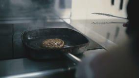 Le cuisinier fait frire une côtelette dans un plan rapproché de poêle banque de vidéos