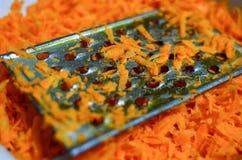 Le cuisinier frotte des carottes sur une râpe illustration de vecteur