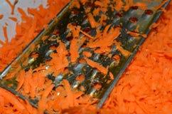 Le cuisinier frotte des carottes sur une râpe illustration libre de droits