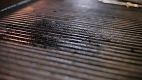 Le cuisinier lubrifie un gril banque de vidéos