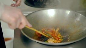 Le cuisinier mélange des crevettes aux légumes dans une poêle Alors il sépare la crevette des légumes banque de vidéos