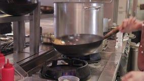 Le cuisinier mélange des légumes dans une casserole de cuisson à la friteuse au-dessus d'un grand feu banque de vidéos