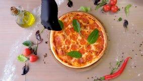 Le cuisinier met des feuilles d'?pinards sur des mains de salami de pizza dans les gants en caoutchouc, plan rapproch? de mains banque de vidéos