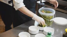 Le cuisinier met des olives dans des cuvettes banque de vidéos