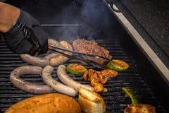 Le cuisinier met dessus le gril assorti par charbons - saucisses, bifteck de viande, légumes et champignons Nourriture de rue images stock
