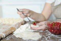 Le cuisinier met le boeuf haché cuit par fourchette dans la pâte Images libres de droits