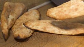 Le cuisinier a mis le shoti traditionnel de pain sur la table avec des bâtons en métal banque de vidéos