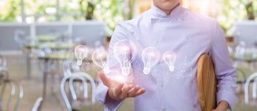 Le cuisinier montre dans les mains d'un burning d'ampoule photo libre de droits