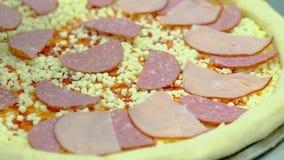 Le cuisinier prépare la pizza avec le lard et la saucisse fumée Ajoute des tranches de lard banque de vidéos
