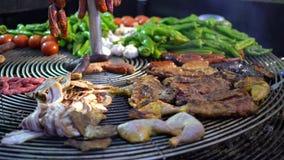 Le cuisinier prépare la viande et des légumes sur un grand gril à la foire le soir clips vidéos